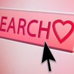 Cursor hovers over a search button with a heart symbol on it - online internet dating / love concept